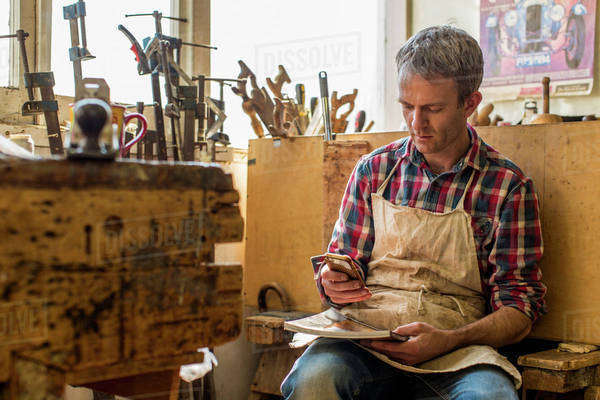 An antique furniture restorer in his workshop, using a smart phone. Royalty-free stock photo