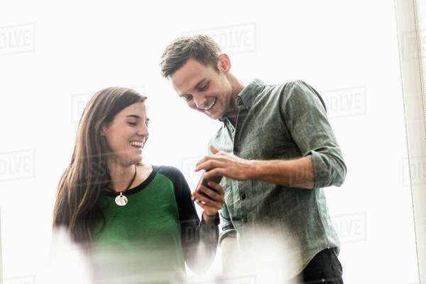 A man and woman talking in an office over coffee. Royalty-free stock photo
