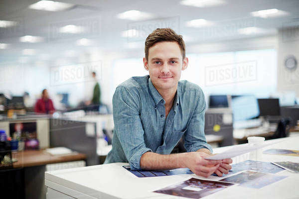 A man smiling and leaning forward on his desk. Royalty-free stock photo