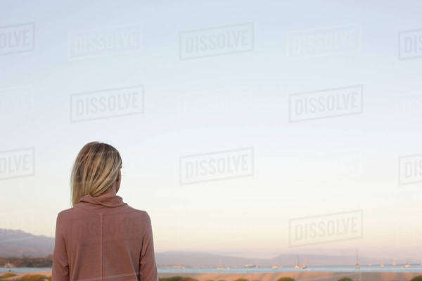 Blond woman standing at the ocean. Royalty-free stock photo