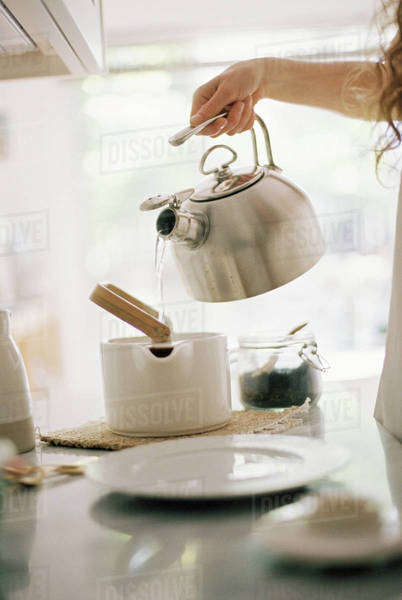 Woman standing in a kitchen pouring hot water from a kettle into a tea pot. Royalty-free stock photo