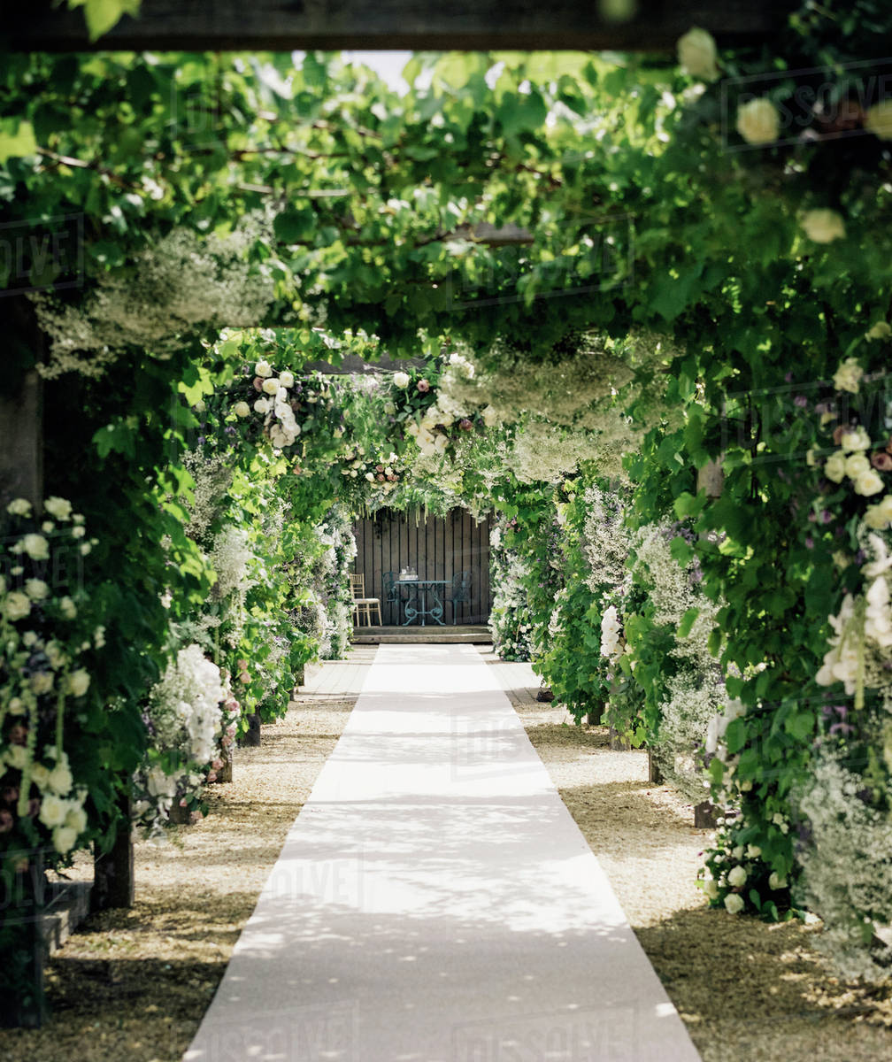 A Garden Path Through An Arch Leading To An Alcove With Table And
