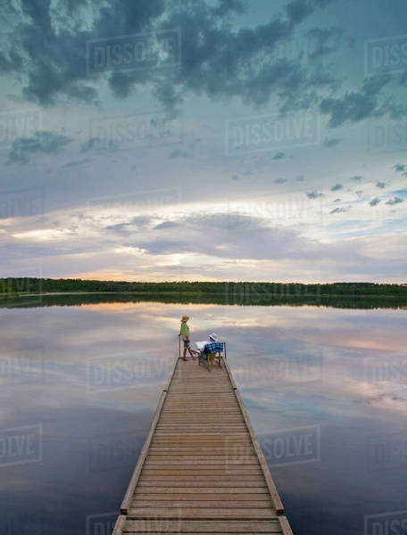 A couple, man and woman sitting at the end of a long wooden dock reaching out into a calm lake, at sunset.  Royalty-free stock photo