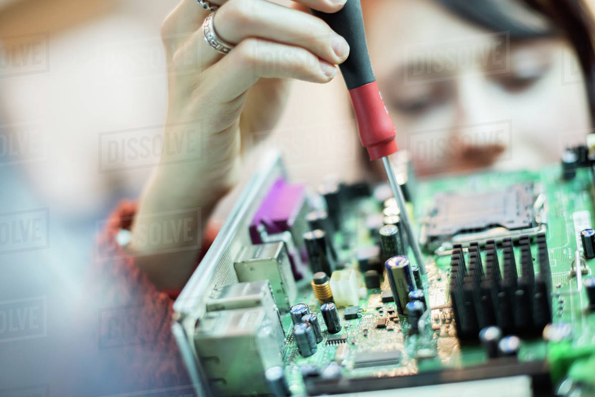 A Woman Using An Electronic Screwdriver On Computer Circuit Board Main Royalty Free Stock Photography Image By Mint Images