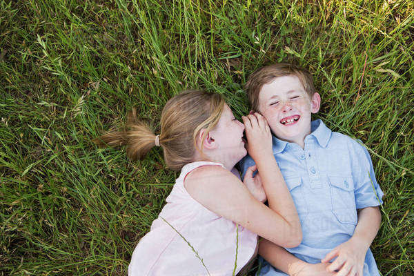 Two children, brother and sister lying side by side on the grass  Royalty-free stock photo