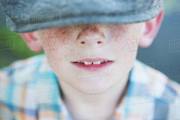 A young boy with a freckled nose, wearing a cap with a large brim.  Royalty-free stock photo