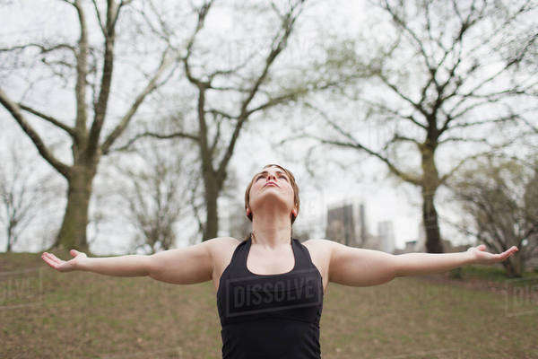 A young woman in Central Park, in a black leotard and leggings, doing yoga. Royalty-free stock photo