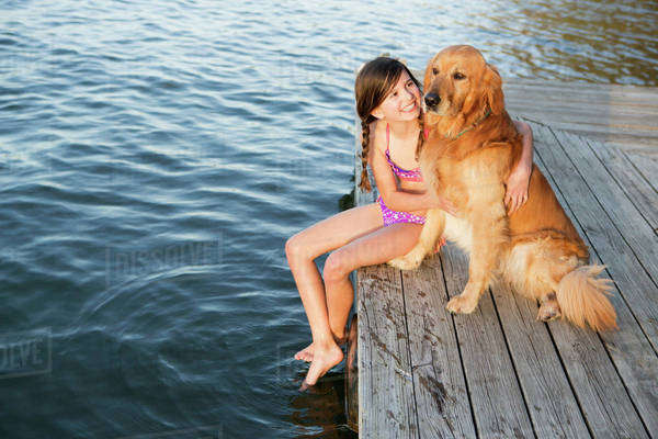 A girl and her golden retriever dog seated on a jetty by a lake. Royalty-free stock photo
