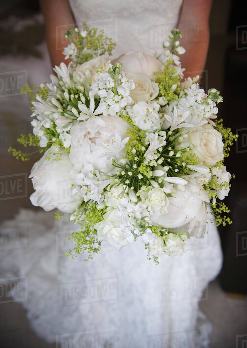 A woman in a white dress a bride holding a bridal bouquet of white a woman in a white dress a bride holding a bridal bouquet of white flowers large white roses and peonies with delicate yellow flowers and green leaves izmirmasajfo