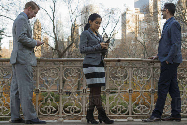 Three people in business clothes standing outdoors. Two men and a woman. Two people checking their cell phones.  Royalty-free stock photo