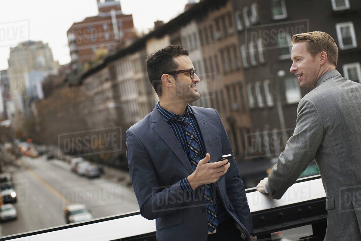 Two men standing talking on an elevated walkway above a city road.  Royalty-free stock photo