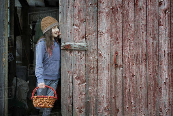 An organic farm in upstate New York, in winter. A girl in a barn doorway with a basket.  Royalty-free stock photo