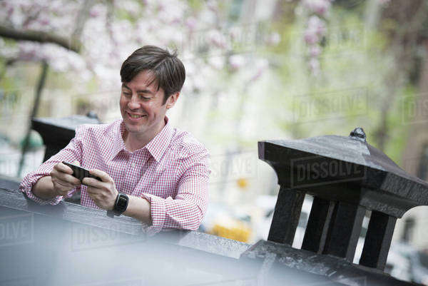 City life in spring. A man sitting outdoors in a city park. Looking down at his smart phone and smiling.  Royalty-free stock photo