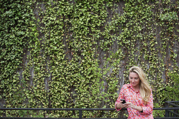 City life in spring. City park with a wall covered in climbing plants and ivy.  A young blonde haired woman checking her smart phone.  Royalty-free stock photo