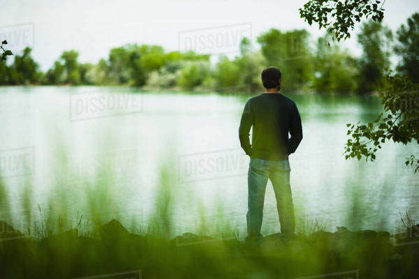 A man standing alone looking into the distance across the water, deep in thought. Royalty-free stock photo