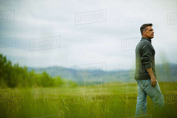 A man standing alone looking into the distance, deep in thought. Royalty-free stock photo