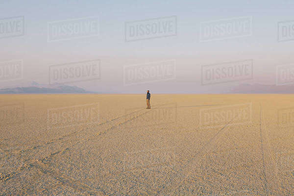 The figure of a man in the empty desert landscape of Black Rock desert, Nevada.  Royalty-free stock photo