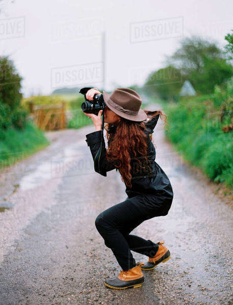 A woman crouching to take a photograph on a country road. Royalty-free stock photo