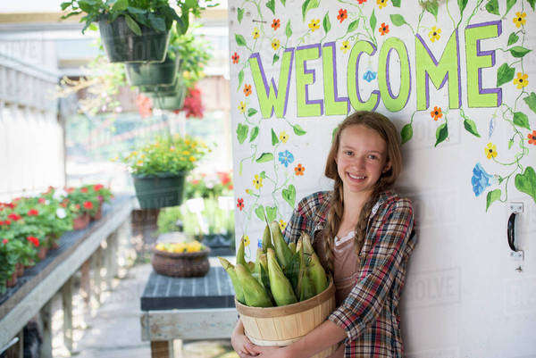 Summer on an organic farm. A girl holding a basket of fresh corn standing by the Welcome sign. Royalty-free stock photo