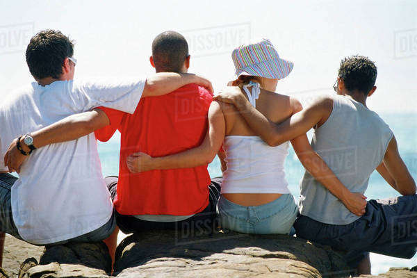 Back view of four friends, with arms around each other, sitting in a row. Royalty-free stock photo