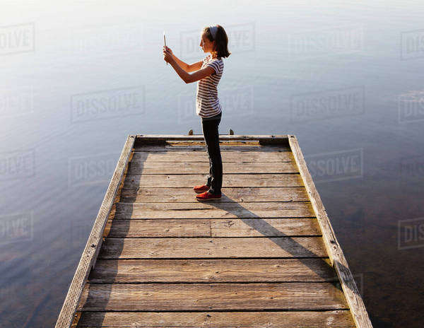 A young girl holding a digital tablet in front of her, standing on a wooden dock over the water. Royalty-free stock photo