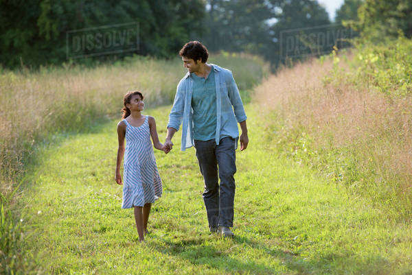 A man and a young girl walking down a mown path in the long grass holding hands.  Royalty-free stock photo
