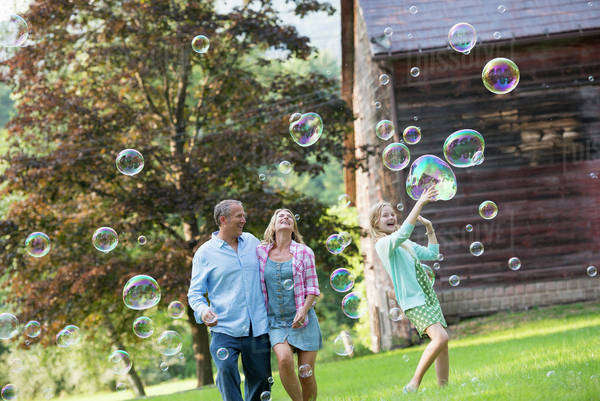A family sitting on the grass outside a bar, blowing bubbles and laughing. Royalty-free stock photo