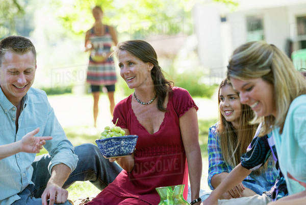 A group of adults and children sitting on the grass under the shade of a tree. A family party.  Royalty-free stock photo