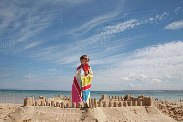 A boy standing beside a sandcastle, on top of a mound of sand. Beach.  Royalty-free stock photo