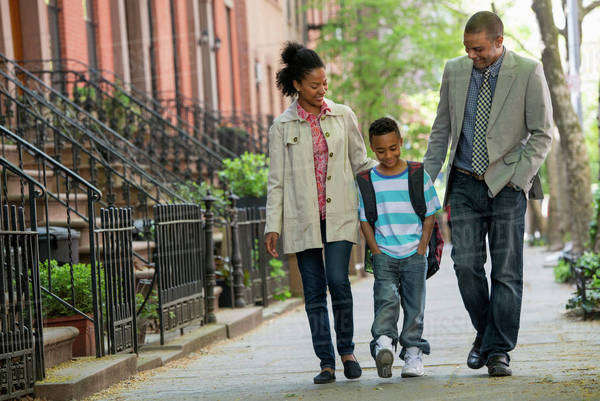 A Family Outdoors In The City. Two Parents And A Young Boy Walking Together.  Royalty-free stock photo