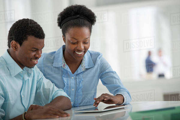 Office Interior. A Man And Woman Sitting Side By Side Using A Digital Tablet. Royalty-free stock photo