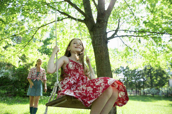 Summer. A girl in a sundress on a swing hanging from a tree branch. A woman behind her.  Royalty-free stock photo