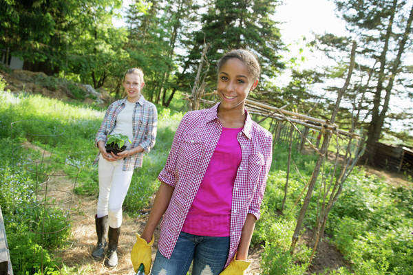 Two girls in a garden, walking up the path, one carrying a plant in a pot.  Royalty-free stock photo