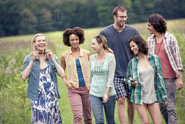 A group of people, two men and four women, walking through the countryside.  Royalty-free stock photo