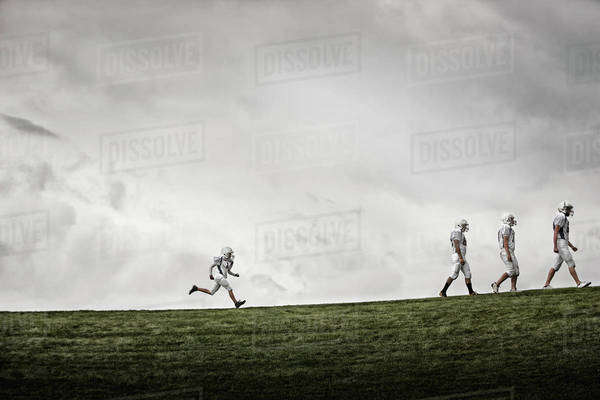 A group of four football players in sports uniform, three tall figures striding along, and one smaller figure running after them.   Royalty-free stock photo