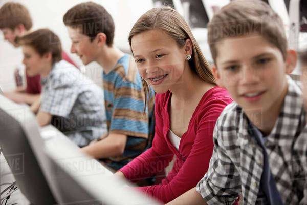 A group of young people, boys and girls, working at computer screens in class.  Royalty-free stock photo