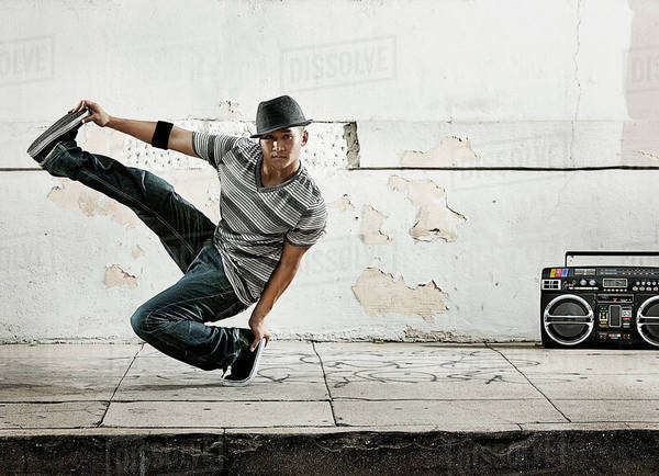 A young man breakdancing, balancing on one foot with his leg outstretched.  Royalty-free stock photo