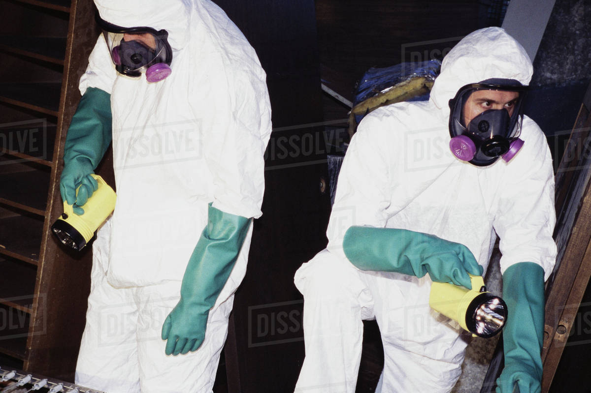 Two men wearing protective clean suits and breathing masks  stock photo