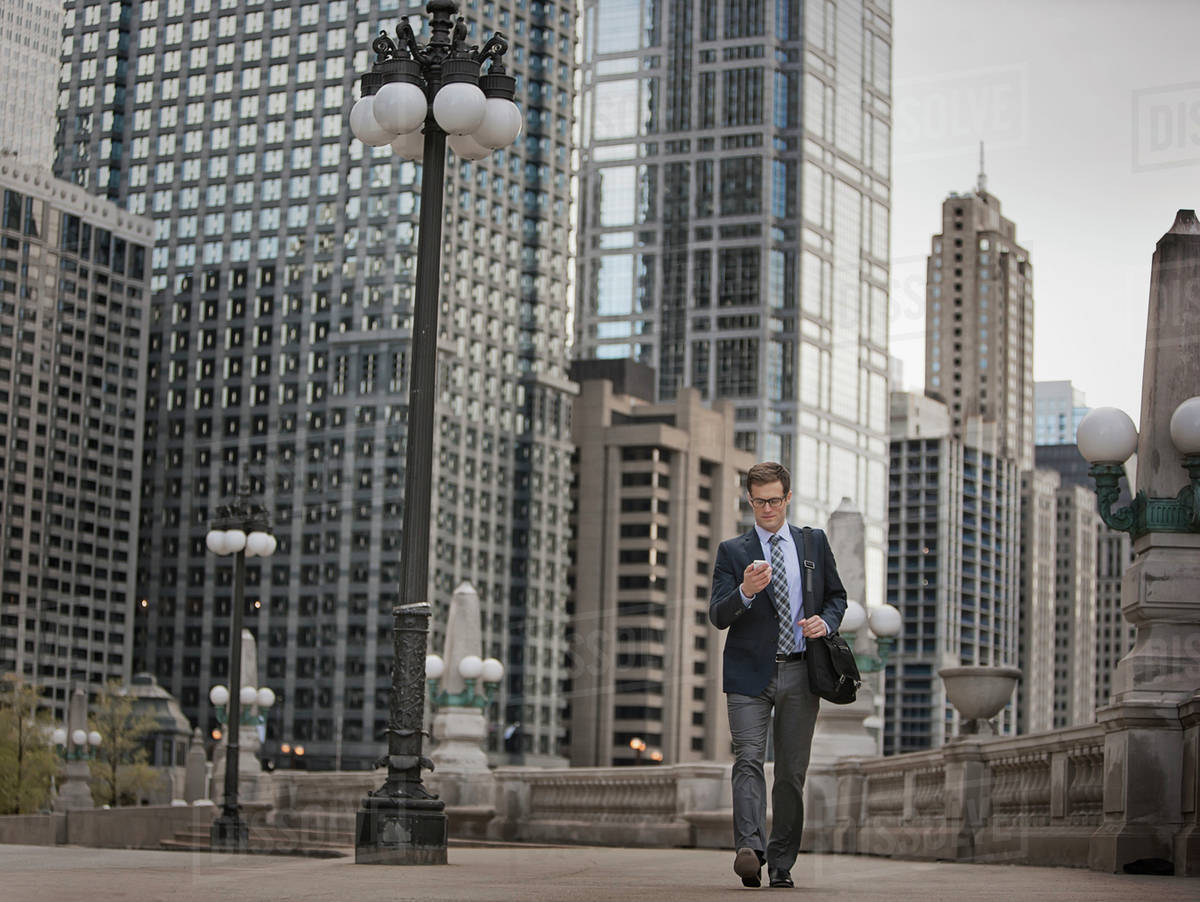 A working day. Businessman in a work suit and tie on a city street, checking his phone.  Royalty-free stock photo