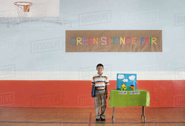 A boy standing under a Green Science Fair sign beside a Solar Power presentation.  Royalty-free stock photo