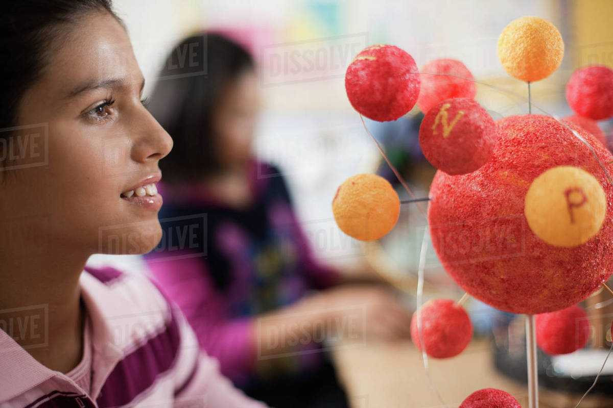 A group of students around a desk in a science lesson, creating molecular models.  Royalty-free stock photo