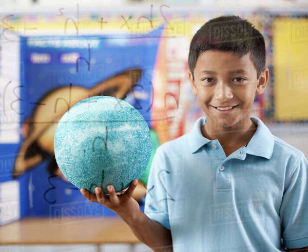 A boy standing by a clear board with scientific equations, holding a globe.  Royalty-free stock photo