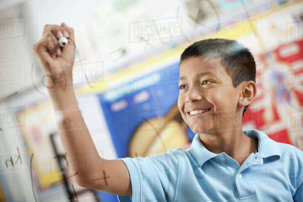 A boy writing scientific equations on a clear perspex board with a felt tip pen. Royalty-free stock photo