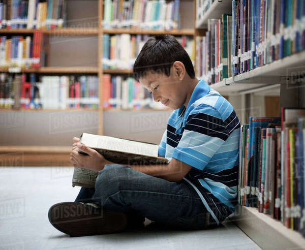 A boy sitting on the floor in a library reading a book. Royalty-free stock photo