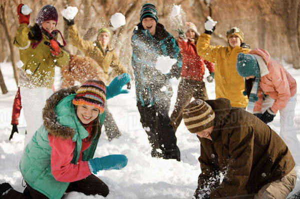 A group of young people, boys and girls having a snowball fight.  Royalty-free stock photo