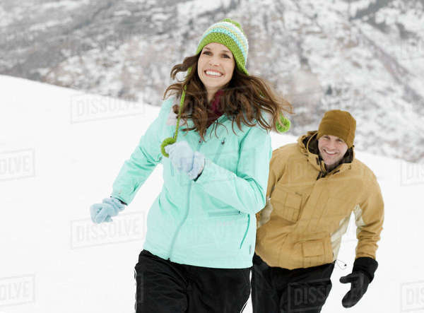 Two people, a couple, in the snowy mountains, chasing each other.  Royalty-free stock photo
