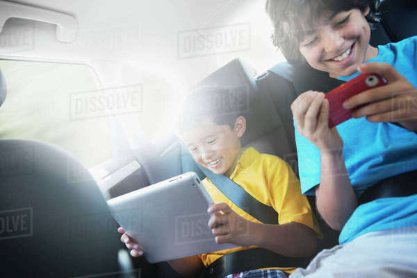 Two children travelling in the back seat of a car, one using a digital tablet and one a handheld game. Royalty-free stock photo