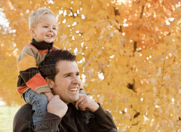 An adult parent and child, father and son under a canopy of orange autumn leaves. Royalty-free stock photo
