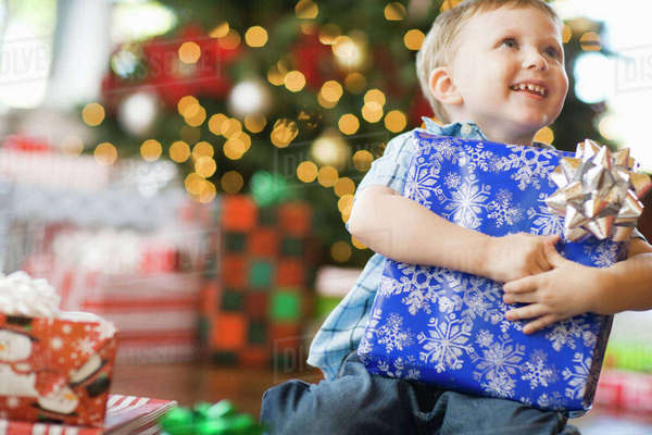 A young boy by a Christmas tree hugging a large wrapped present.  Royalty-free stock photo