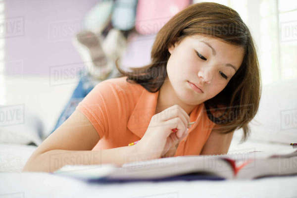 A girl lying on her bed reading a book.  Royalty-free stock photo